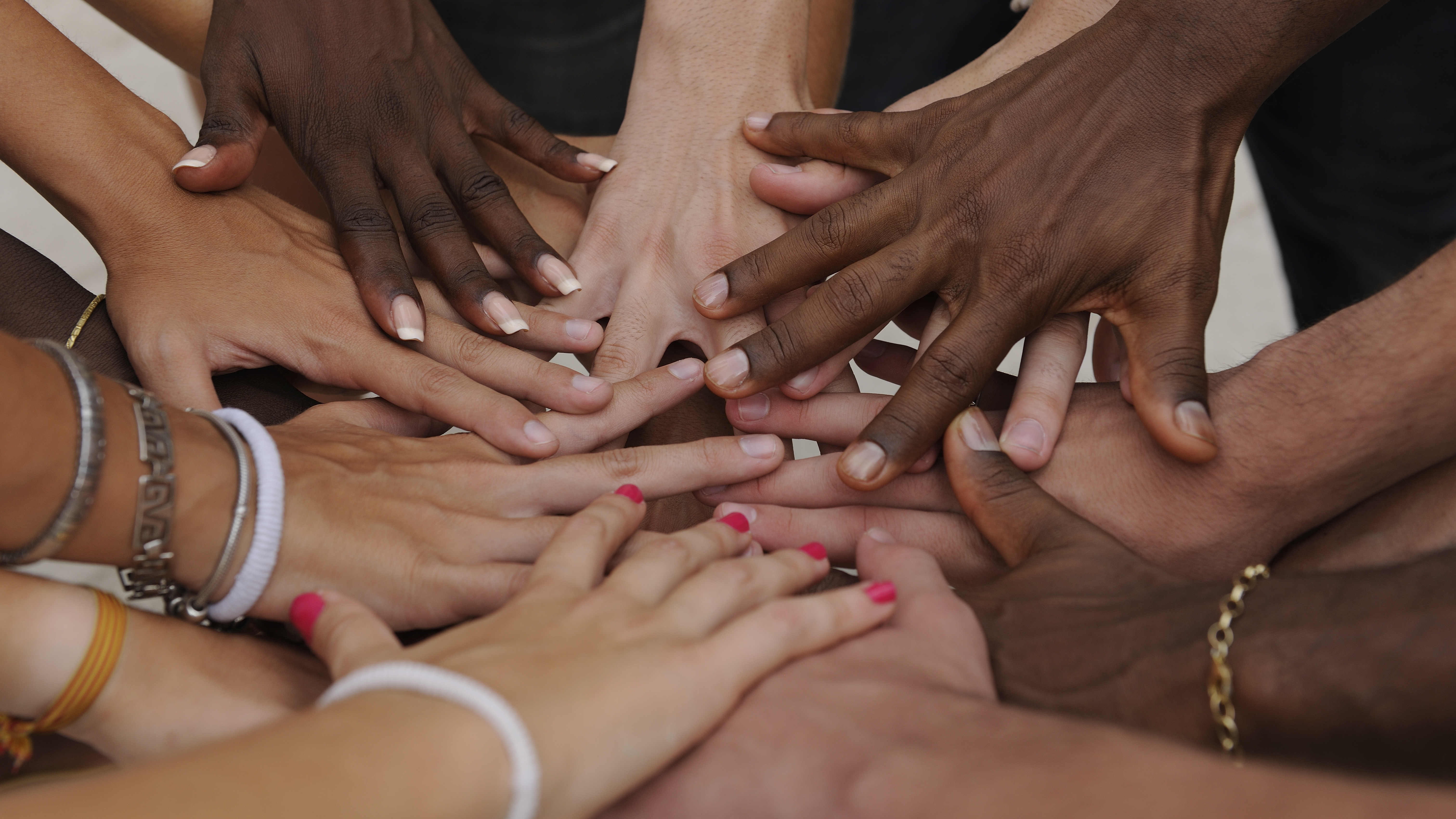 a circle of hands coming together in the middle before a cheer
